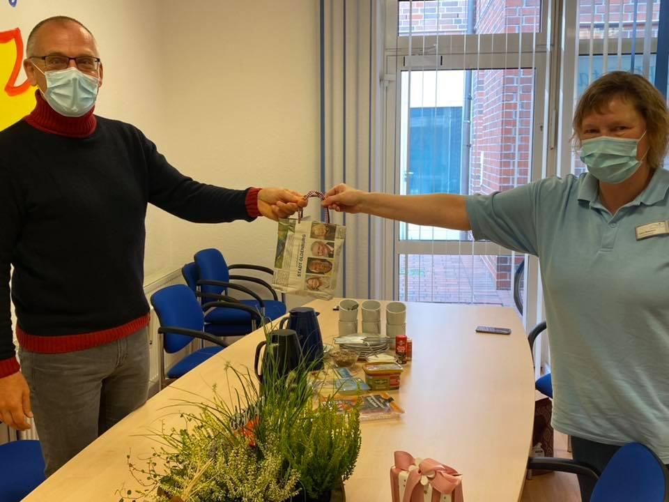 Kolleginnen überreichen unserem Verwaltungsmitarbeiter ihr Geschenk zum Fünfjährigen.